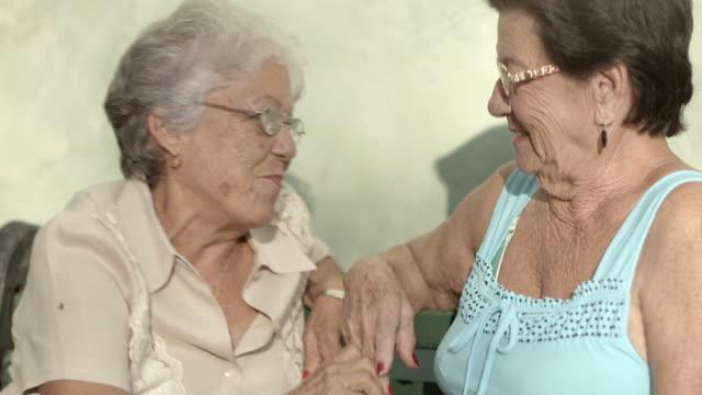 vídeos de stock, filmes e b-roll de velhos amigos, dois feliz sênior mulher falando no parque - sul europeu