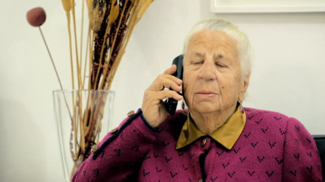 Old granny of eighty-three years old talking to her friend on a phone while sitting on a chair in the room. video