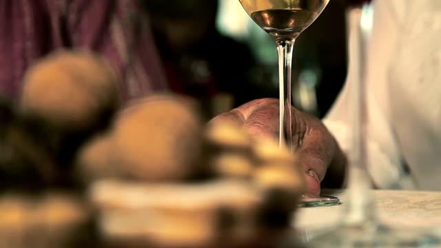 vidéos et rushes de hd: vieille mains et un verre de vin - diner entre amis