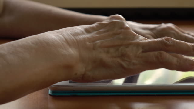 Old hands operating a tablet computer video