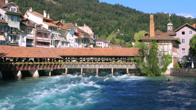 Old, historical wooden bridge in Thun over Aare river, turquoise water, cityscape of alpine town. Switzerland