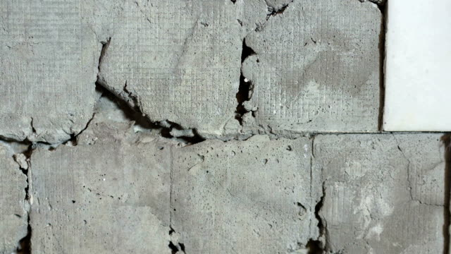 Old house interior ceramic tiles falling off from the wall in the bathroom video