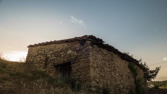 Antigua casa de roca y piedras timelapse de puesta de sol en un pequeño pueblo de España cuenca - vídeo