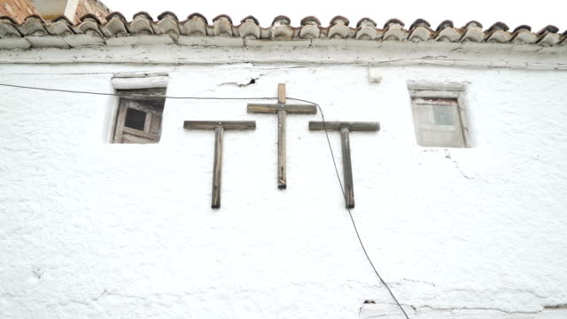 Old house with religious cross. Black cat in the window