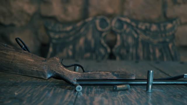 vidéos et rushes de vieux fusil de chasse se trouve sur la table. sur la table sont les obus et cartouches (couleur froide) - coquille et coquillage