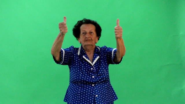 yaşlı bayan yeşil ekranda başparmak kadar veriyor. - thumbs up stok videoları ve detay görüntü çekimi