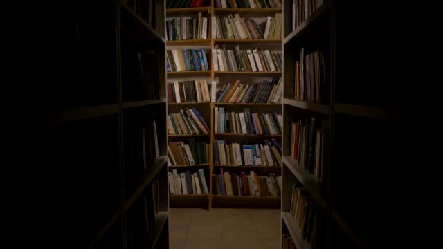 stockvideo's en b-roll-footage met oude bibliotheek. de camera beweegt langs twee hoge boekenkasten. cinematografisch kader. voor horror verhalen, gearchiveerde video's en films. schappen met boeken. - boekenkast
