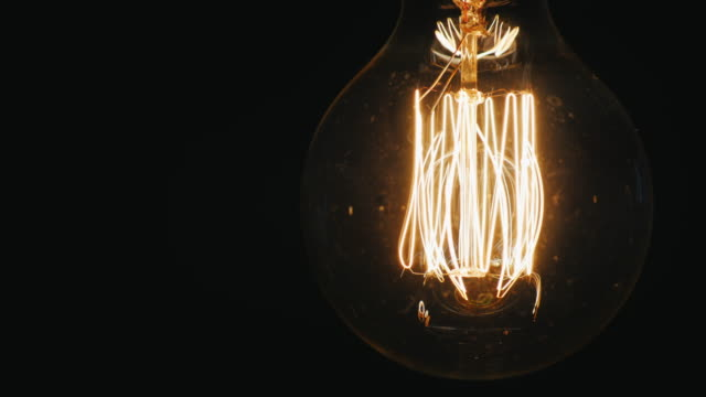 Old light bulb lights up continuously. On a black background, slightly swaying video
