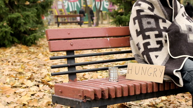 Old lonely poor person sitting on bench in park and asking for alms, poverty video