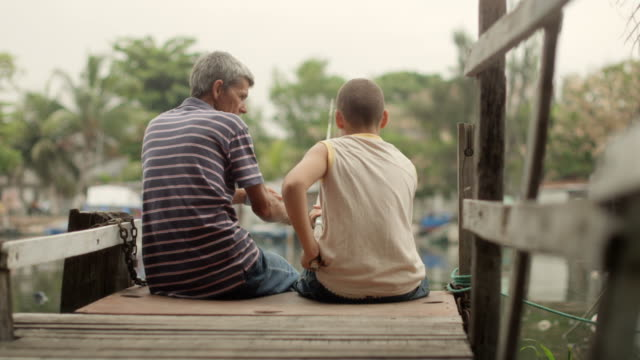 Old man and boy fishing together for fun on river video