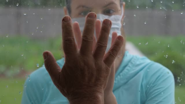 Old Man And Woman Touch Palms Of Their Hands Through Glass Window In Quarantine
