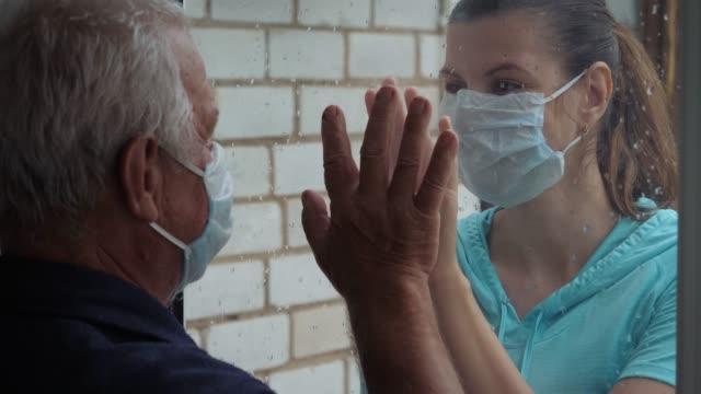 yaşlı adam ve kadın karantinada cam pencereden ellerinin avuçlarını dokundu - ziyaret stok videoları ve detay görüntü çekimi