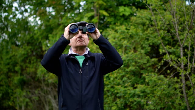 Old Man Birdwatching With Binoculars