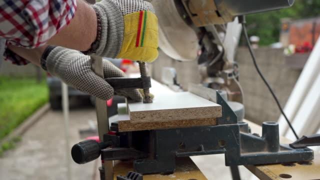 alter mann klemmt holzdielen vor dem schneiden - kreissäge stock-videos und b-roll-filmmaterial