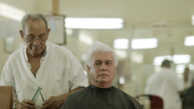 vidéos et rushes de vieil homme coupe de cheveux au client dans le salon de beauté pour hommes - salons et coiffeurs