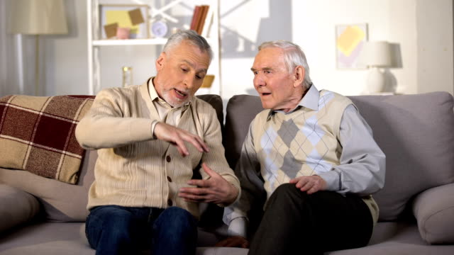 old man explaining something to deaf friend, sitting on sofa at home, problems - sordità video stock e b–roll