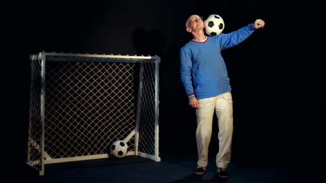 Old Man Is Holding Soccer Ball On His Shoulder video
