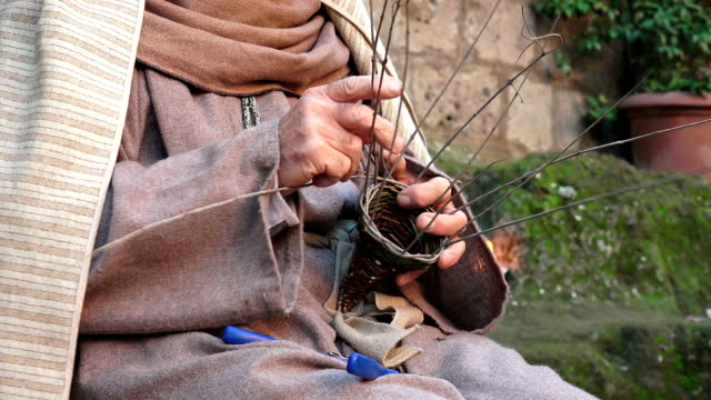 old man is making a basket by hand