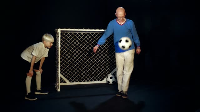 Old Man Is Showing His Soccer Skills To Young Footballer