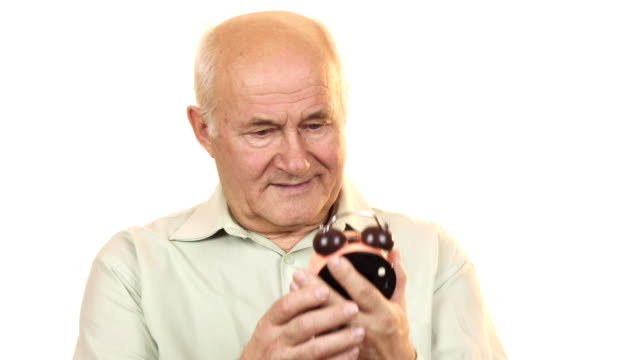 Old man looking at an alarm clock smiling to the camera video