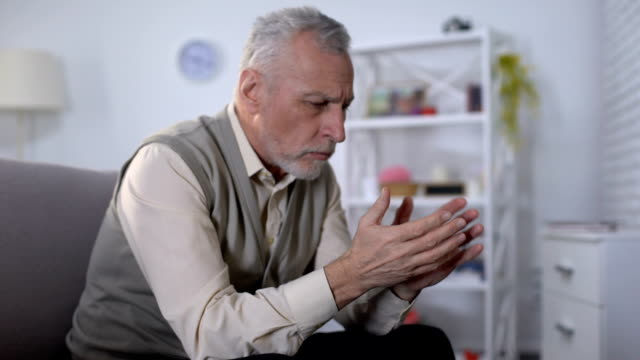 Old man looking at hand trembling, distressed by tremor, early Alzheimer symptom Old man looking at hand trembling, distressed by tremor, early Alzheimer symptom shivering stock videos & royalty-free footage