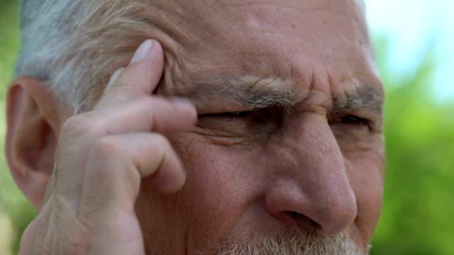 vídeos de stock e filmes b-roll de old man massaging temples feeling throbbing pain, problems with blood pressure - enfarte