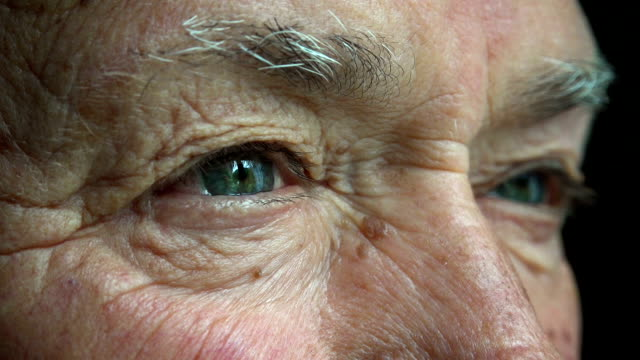 old man opens his eyes: closeup portrait video