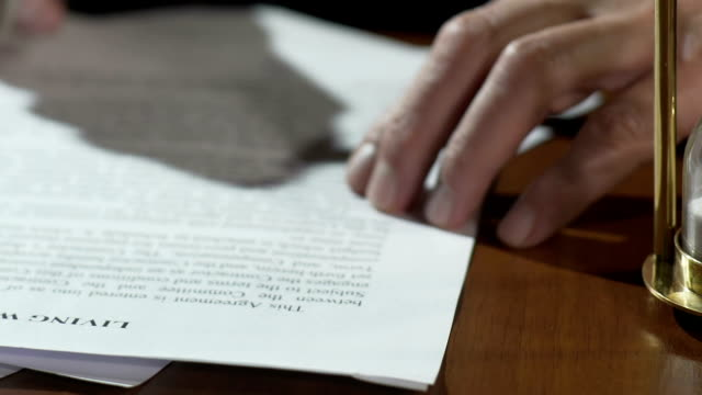Old man reading and signing living will papers, sand flowing in hourglass table video