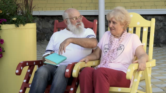 Old man reads a book a wife and kisses her in cheek, relaxing in rocking chairs video