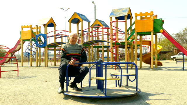 old man rides a carousel in a deserted children's park