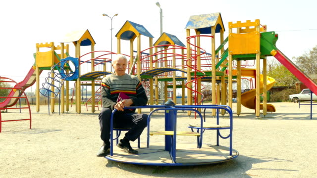 old man rides on a children's carousel in an empty playground