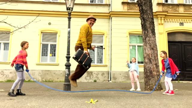 vídeos de stock e filmes b-roll de old man rope skipping with three girls. - crianças todas diferentes