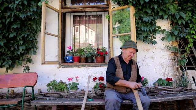 stockvideo's en b-roll-footage met oude man verscherping bijl - dorp