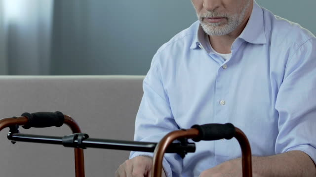 Old man sitting and looking at walking frame, spine trauma, indecisiveness video