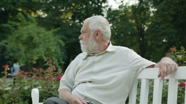 Old Man Sitting on a White Bench in the Park video