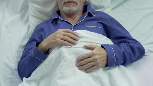 Old man sweetly sleeping in bed, turning over on other side, enjoying comfort video