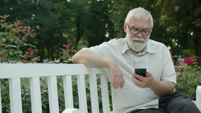 Old Man Using a Phone Outdoors video