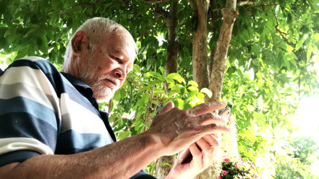 Old man using a smartphone outdoors video