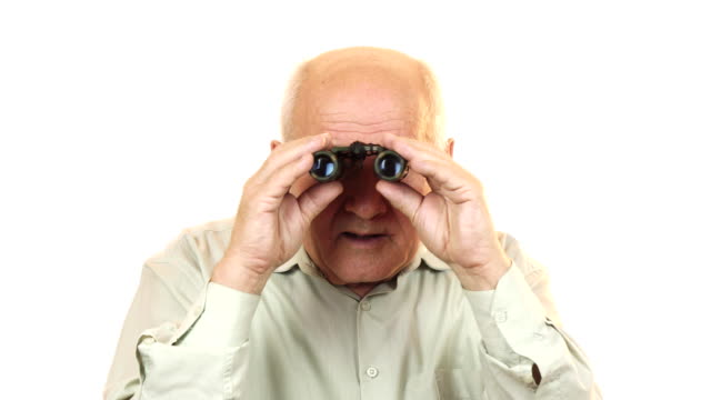 Old man using binoculars looking surprised to the camera Senior man using binoculars looking shocked and surprised to the camera isolated on white seniority spying searching observing travelling emotion expressive retirement hobby leisure lifestyle. magnifying glass stock videos & royalty-free footage