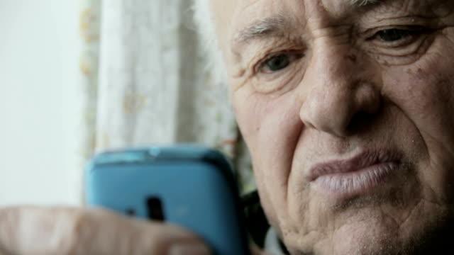 vídeos de stock e filmes b-roll de old man using new technology: mobile phone, cell phone, smartphone - old men window