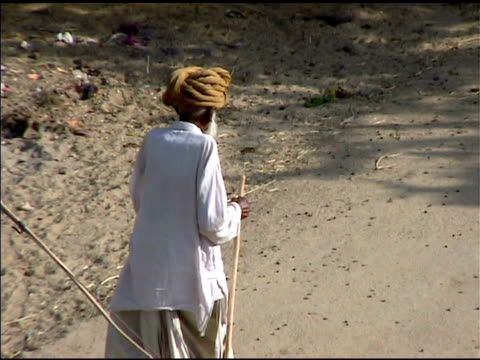 Old man walking with staff in India video