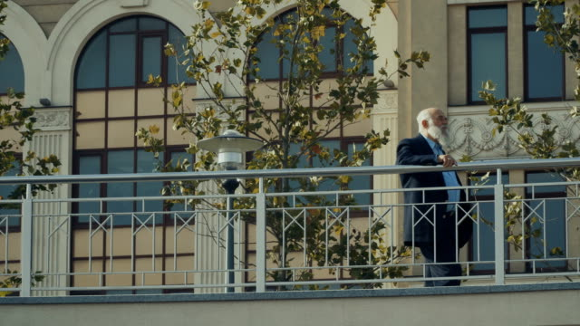 Old man wearing suit looks at the city video