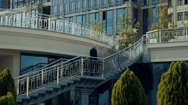 Old man wearing suit walks upstairs video