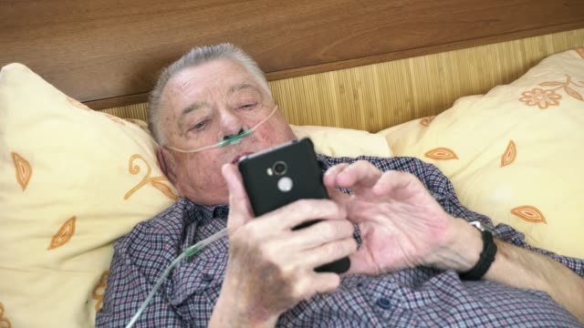 Old man with nasal cannula is laying in the bed with phone in hands Old man with nasal cannula is laying in the bed with phone in hands. The man is pushing the screen of the phone and takes deep breathes. Concept of medical treatment of lung diseases. emphysema stock videos & royalty-free footage