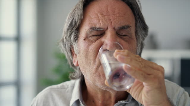 old man with sensitive teeth holding a glass of cold water - denti video stock e b–roll