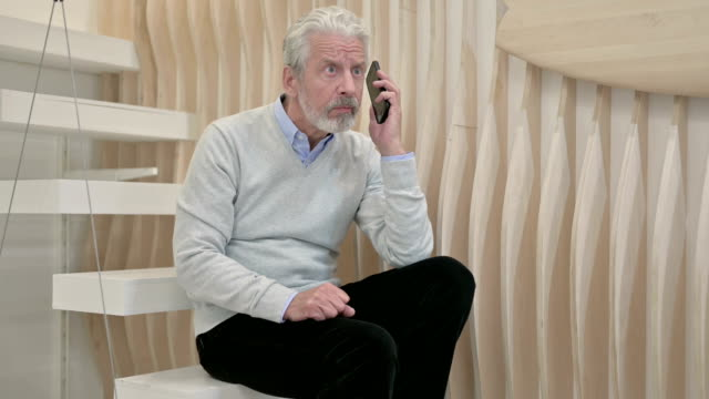 old man yelling in anger during phone talk, negotiating - rabbia emozione negativa video stock e b–roll