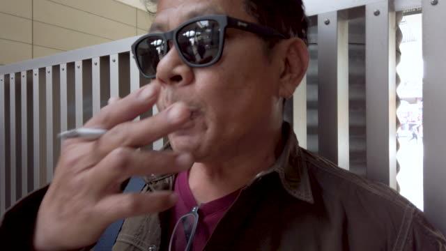 Old men with sunglasses smokes cigarette