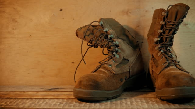 Old military boots on a wooden table Old brown military boots on a bright wooden table made of boards veteran stock videos & royalty-free footage