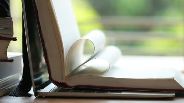 vídeos de stock e filmes b-roll de old open book on desk with heart shape on blur green background in page for reading. research literature for learning education concept - filosofia