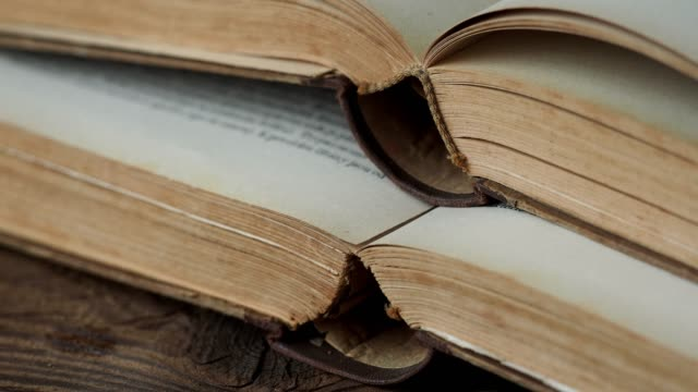 Old open books on wooden table